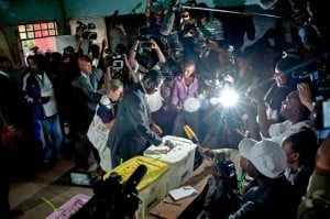 Journalists and polling staff look on as Kenya's then Prime Minister Raila Odinga, casts his vote on March 4, 2013. Photo: AFP/Will Boase
