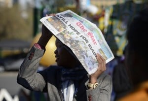 A journalists protects his head from the sun while waiting outside the hospital where South Africa's former president Nelson Mandela was being cared for in June 2013. Photo: AFP/Eric Feferberg