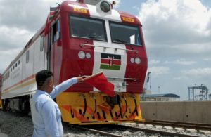A man waves a red flag during the launch of the first batch of Standard Gauge Railway freight locomotives at Mombasa Port, Kenya, on January 11, 2017. The locomotives are expected to boost the capacity of Kenya's railway transportation, assisting in the realization of Kenya's economic development goals. The SGR system, the biggest infrastructure project in Kenya since independence is being built by the state-owned China Road and Bridge Corporation (CRBC). / AFP PHOTO / ANDREW NGEA