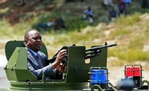 Kenyan President Uhuru Kenyatta stands inside an armoured personal carrier during the commissioning of 500 police vehicles at Nairobi's Uhuru Park on January 16, 2017. President Kenyatta said the Armoured personal carriers will help Kenyan police to counter the terrorism in the country. Kenya is preparing for General Elections on August 8, 2017. / AFP PHOTO / JOHN MUCHUCHA