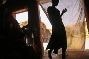 A 23-year-old Sudanese woman holds a glass of her homemade alcoholic brew in Halfaya near Khartoum. A Muslim woman, she has been stigmatised as a criminal for brewing and selling illicit alcohol. Photo: AFP/Khaled Desouki