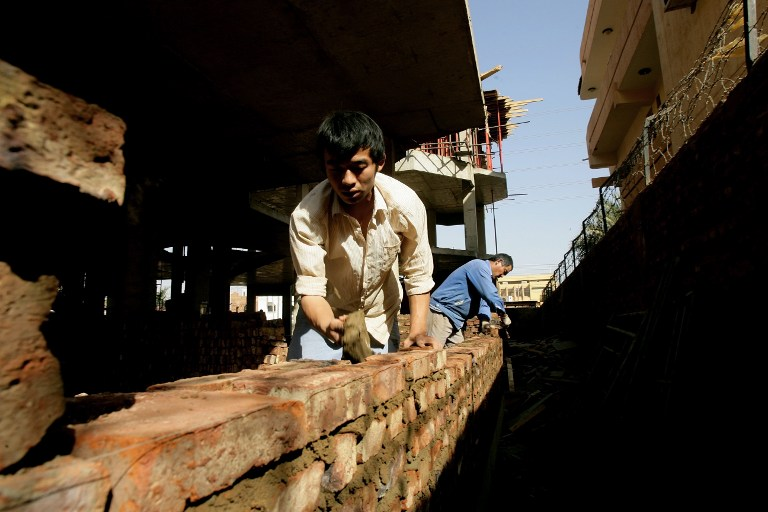 Chinese workers build a wall at a construction site in the capital of Sudan in February 2012. In 2013, the Chinese ministry of commerce reported that more than 2,000 Chinese companies operated on the African continent. Photo: AFP/ASHRAF SHAZLY