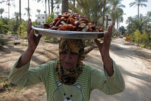 A Palestinian woman carries a pile of freshly harvested dates on her head. Photo: AFP/Said Khatib