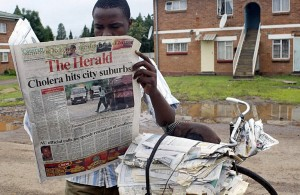 A Zimbabwean newspaper vendor reads a state owned paper in Harare. Photo: Desmond Kwande/AFP