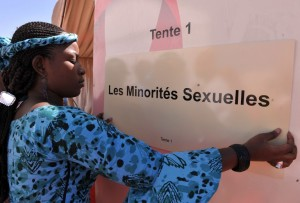 """A hostess hangs a sign saying """"Sexual Minorities"""" at the entrance to a tent where a workshop on """"sexual minorities"""" will be held, on December 4, 2008 in Dakar during the International Conference on AIDS and Sexually Transmitted Diseases in Africa (Icasa). AFP PHOTO / SEYLLOU"""