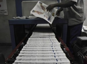 Copies of China Daily roll of a printing press in Nairobi. Photo: AFP/Tony Karumba