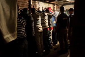 A group of men stand with their hands against the wall after the house where they were gambling was raided during a combined Metro Police and South African Police Services operation to arrest suspects, and search for drugs and firearms, in Manenburg, on August 27, 2013. Photo: AFP/Rodger Bosch