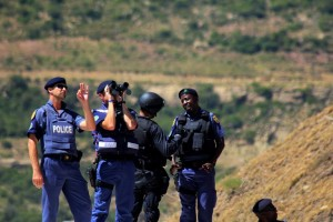 Members of the South African Police keep watch over a campaign rally  in Maseru. Photo: AFP/Hlompho Letsielo