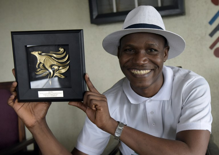 Nigerian Wellington Jighere holds his English-speaking World Scrabble Championships award in November 2015. Photo: AFP/PIUS UTOMI EKPEI
