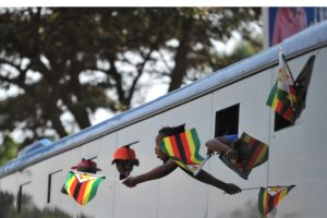 Supporters of Zimbabwe's incoming president Emmerson Mnangagwa, wave Zimbabwean flags from a bus as they arrive at the ruling Zanu-PF party headquarters in Harare on 22 November 2017. Photo: AFP/TONY KARUMBA