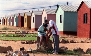 A young couple outside a row of new houses in Sebokeng some 60 km south of Johannesburg 15 April 1999. Officials then said some 681 200 houses had been built or were under construction since the 1994 elections.