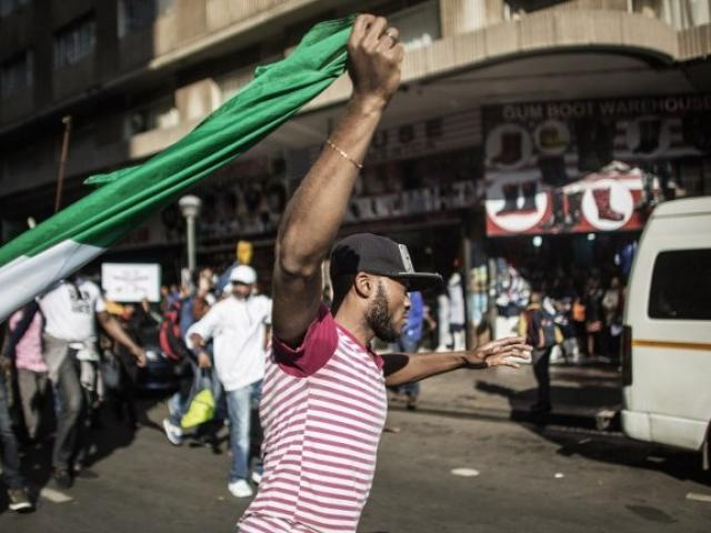 A man holds a Nigerian flag as thousands march through the streets of Johannesburg against the wave of xenophobic attacks that took place in South Africa in 2015. Photo: AFP/GIANLUIGI GUERCIA