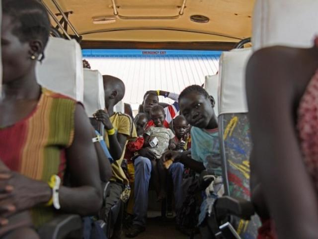 Newly arrived refugees from South Sudan sit in a bus at the Elegu Collection Centre in Amuru, Uganda, in July 2016. Photo: AFP/Isaac Kasamani