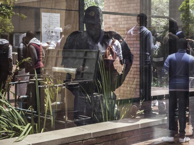 A police officer checking his phone is reflected in a window as students from the University of Witwatersrand's medical school gather after clashes during a protest for free high education in October 2016 in Johannesburg, South Africa. Photo: AFP/GIA