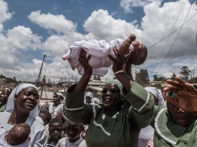 Church members carry newborn twin girls to induct them as new members of the Neema indigenous church in February 2016 in Nairobi. Photo: AFP/FREDRIK LERNERYD
