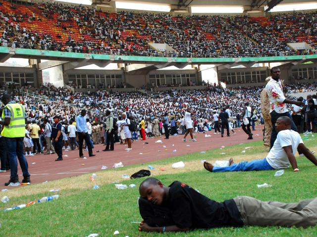 Job-seekers lie on the pitch after a stampede in Abuja National Stadium, where thousands of people came to apply for work at the Nigerian immigration department in March 2014. At least seven people were killed and dozens injured. Photo: AFP