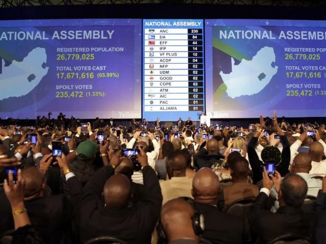 People react as electronic results boards reflect the number of National Assembly seats allocated to various political parties during the formal announcement of the National and Provincial Election Results at the Independent Electoral Commission (IEC