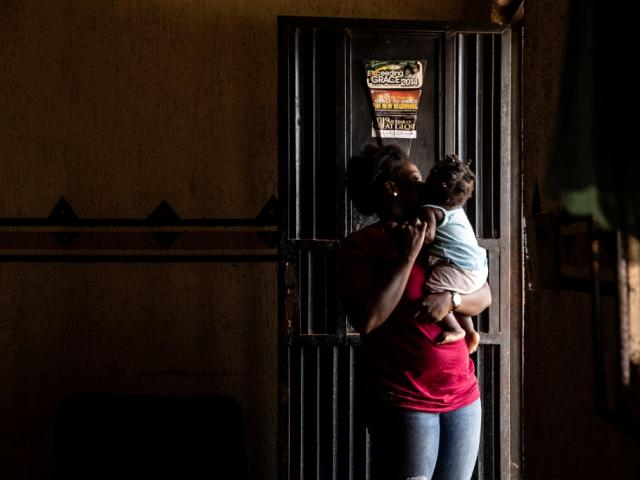 A woman and her child stand by a door on June 26, 2019 in Benin City, at one of the shelters of the Society For the Empowerment Of Young Persons (SEYP), an organisation that rehabilitates and reintegrates women returning from Libya carrying young children often born as the result of rape. (FATI ABUBAKAR/AFP)