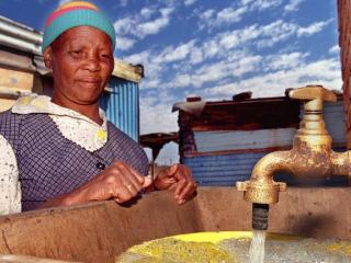 Ms Anna Jacobs fills her bucket with water from a tap placed by the government next to her house in this April 1999 file picture. As the world marks World Water Day on 22 March, for many in Africa, water access remains a key challenge. Photo: ODD AND